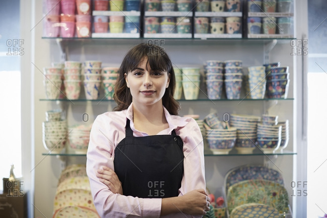 Portrait of confident saleswoman standing with arms crossed against crockery at boutique