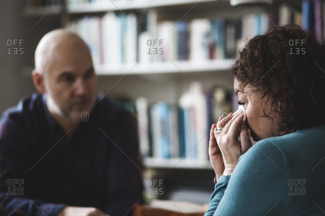 Close-up of crying mature patient sitting with therapist at home office