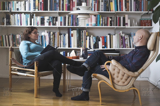 Mature female therapist talking to patient by bookshelf at home office