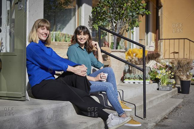Full length portrait of smiling female partners sitting on steps outside store