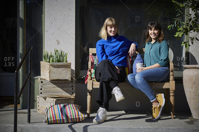 Full length portrait of smiling owners sitting on bench outside store