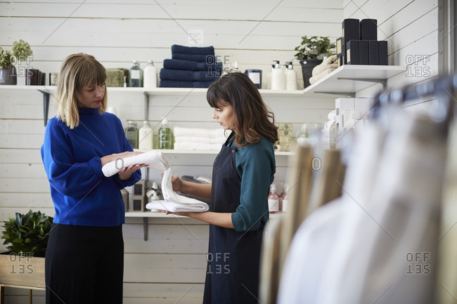 Female owner assisting customer in choosing textile at store