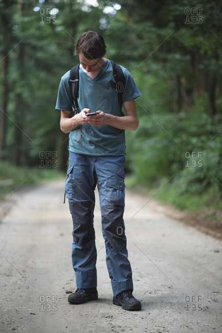 Man looking down at cell phone on forest path