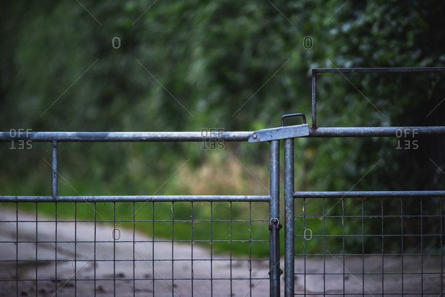 Metal gate closed in front of rural drive