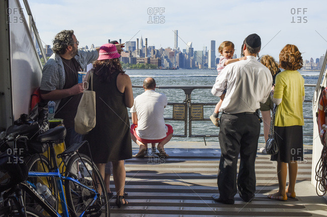 New York City, New York, USA - May 29, 2016: Tourists viewing the Manhattan skyline from the East River Ferry