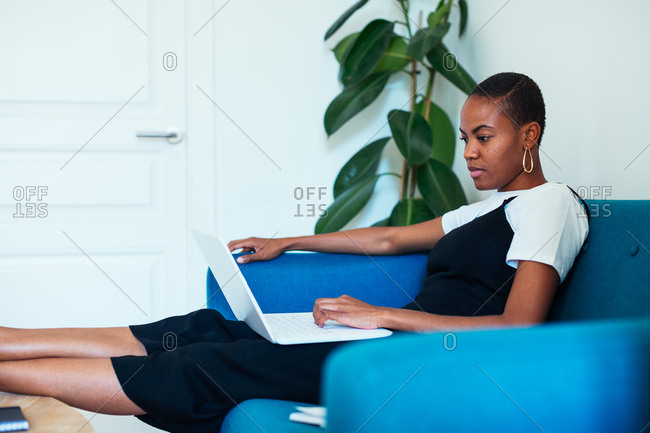 Young woman sitting on couch using her laptop