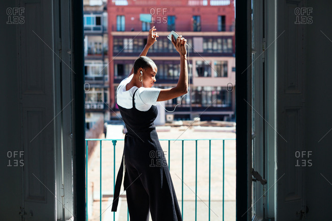 Young woman on balcony listening music and dancing