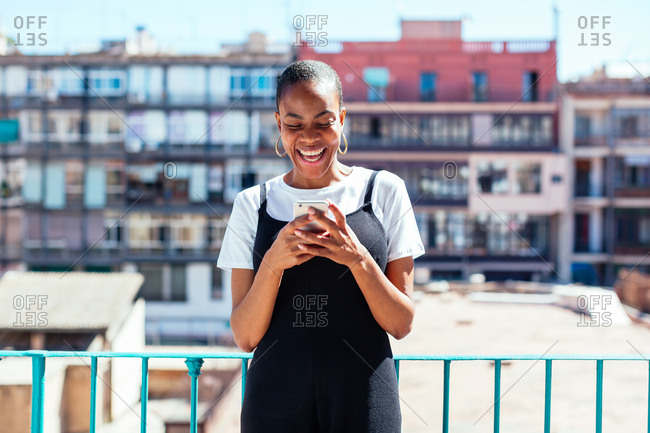 Young woman on balcony laughing whilst using her phone