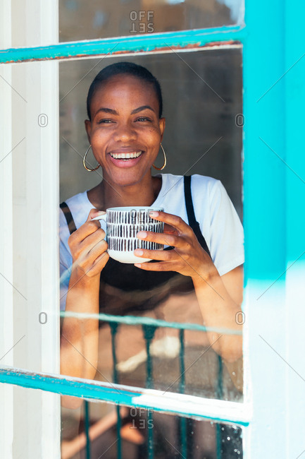 Smiling woman holding a cup of coffee smiling through the window