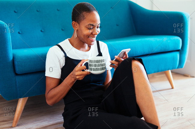 Young woman sitting on floor using her phone at home