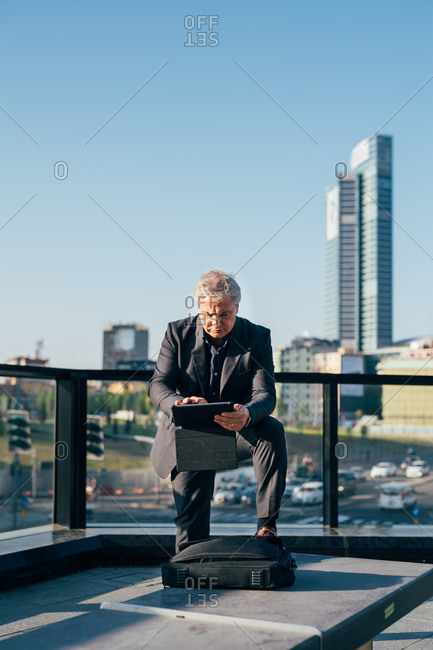 Middle-age contemporary businessman using a tablet on a balcony in the city