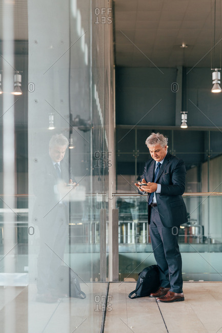 Middle-age businessman using a smart phone indoors