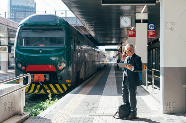 Middle-age businessman talking on a smart phone and using a tablet in a railway station