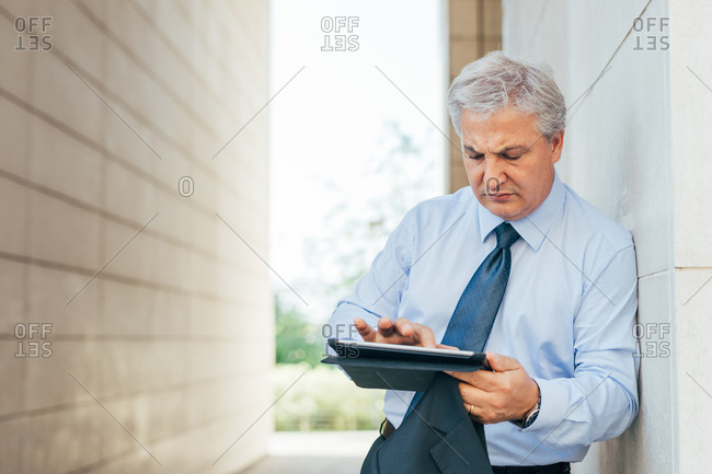 Middle-age contemporary businessman using a tablet outside