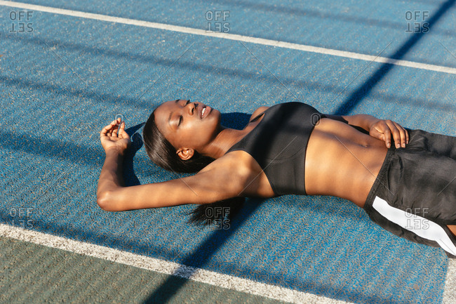 Young woman resting in sports court
