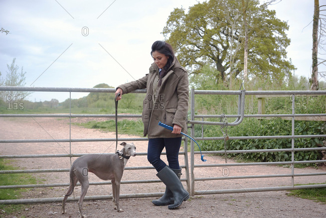 Woman with dog leaning on rural gate