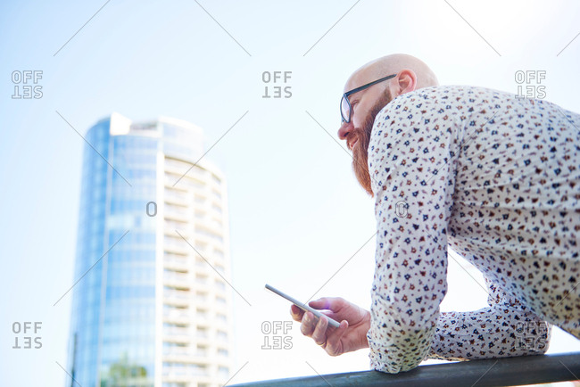 Man holding smartphone in business area