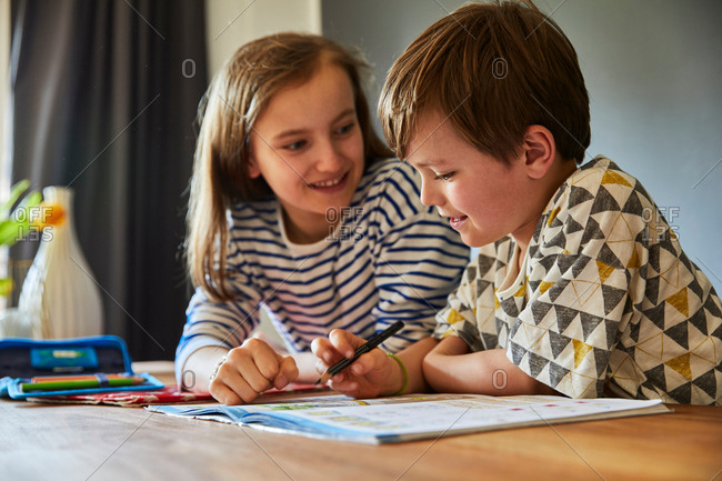 Girl helping brother with homework