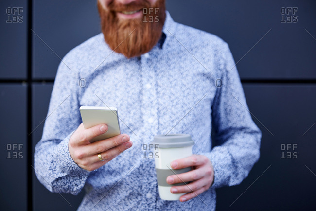 Bearded man texting on smartphone, cropped
