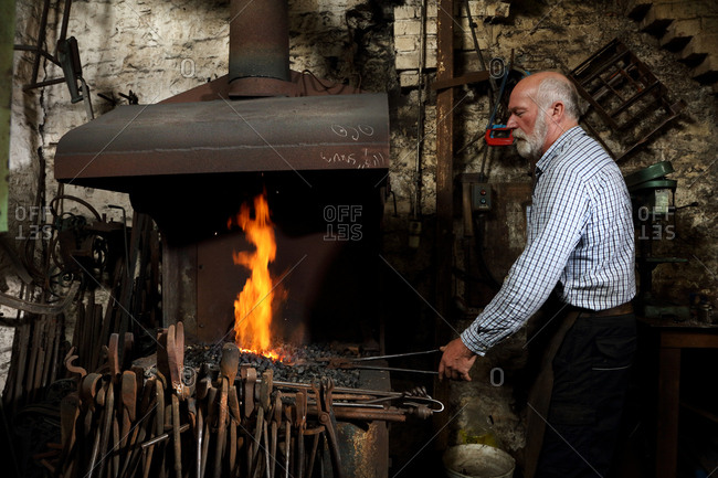 Blacksmith heating metal in forge fire in blacksmiths shop