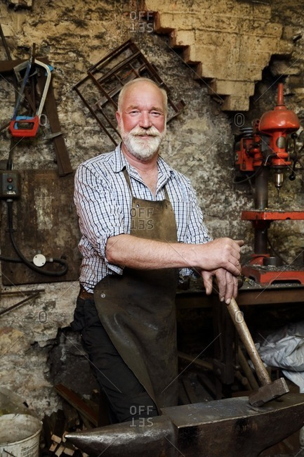 Blacksmith with hammer and anvil in blacksmiths shop, portrait