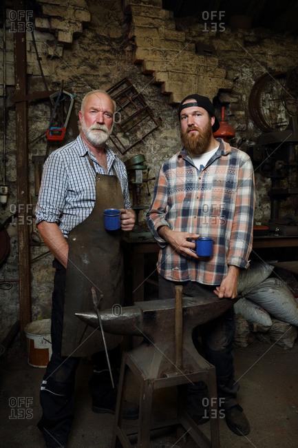Senior blacksmith and son taking a break in blacksmiths shop, portrait