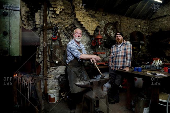 Senior blacksmith and son in blacksmiths shop, portrait