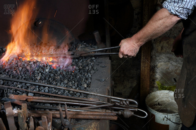 Blacksmith heating metal in forge fire in blacksmiths shop, cropped