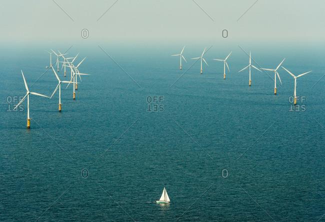 Sailing boat sails close to windfarm, IJmuiden, Noord-Holland, Netherlands