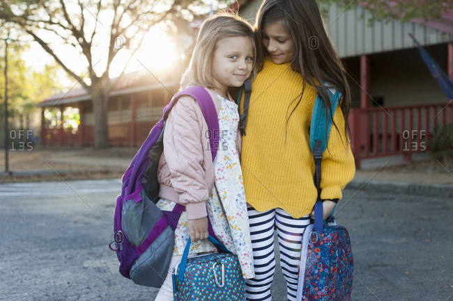 Two sisters outside their school before classes begin