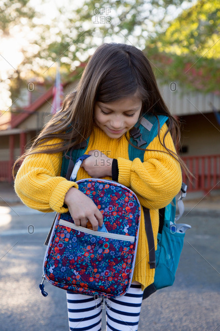 A girl packs a snack in her lunch box before school