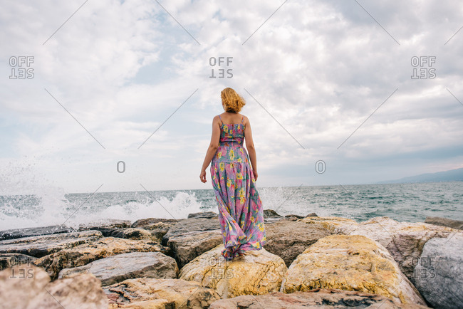Back of young woman wearing colorful dress standing on rocky beach