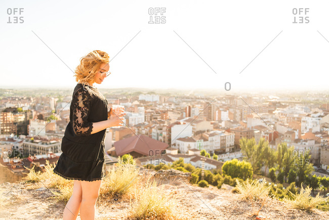 Girl drinking water while walking in park overlooking city at sunset