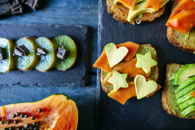 Kiwi with chocolate and bread with avocados and papaya on table
