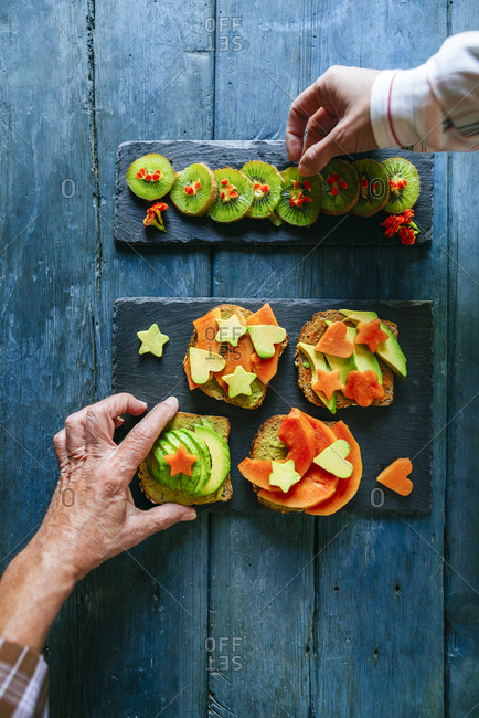 Hands picking kiwis and bread with avocados and papaya