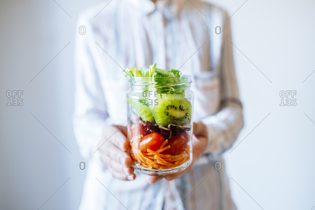 Close-up of woman holding salad pot of lettuce, kiwi, tomatoes, endive and carrot