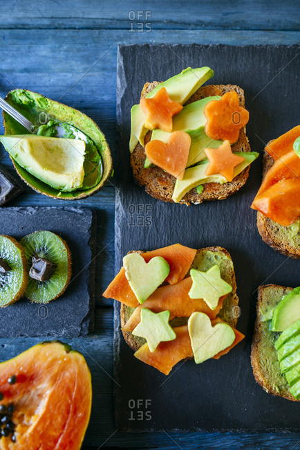 Avocado toast with papaya served with kiwi and chocolate