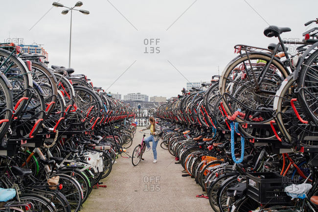 Amsterdam, Netherlands - June 12, 2018: A young woman fetches her bike at the Centraal station