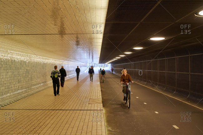 Amsterdam, Netherlands - June 12, 2018: People bike and walk underneath the central train station