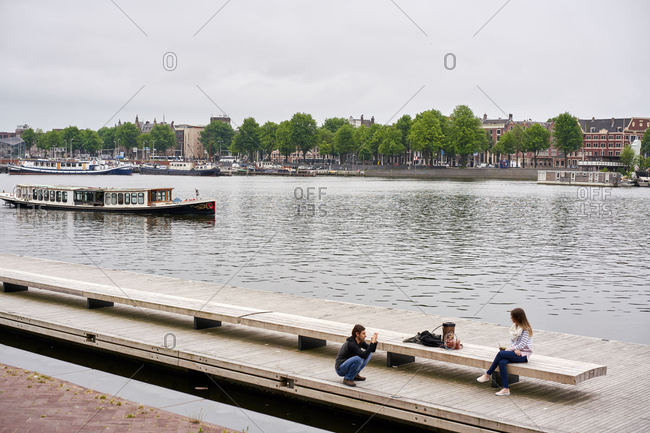 Amsterdam, Netherlands - June 12, 2018: Tourists taking photos along a body of water near Amsterdam Centraal station