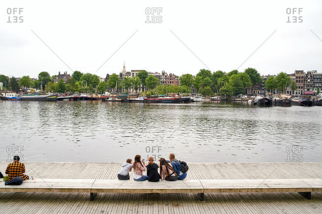Amsterdam, Netherlands - June 12, 2018: A group of young girls sit on a bench near the water