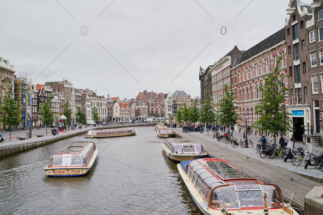 Amsterdam, Netherlands - June 12, 2018: Canal boats in the water in the city centre