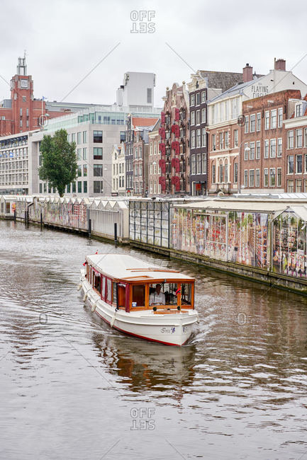 Amsterdam, Netherlands - June 12, 2018: An old-fashioned canal boat on the Singel canal at the flower market