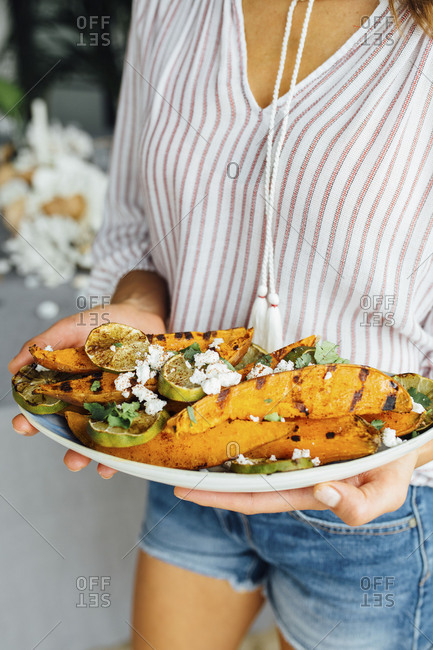 Woman holding plate of grilled sweet potatoes