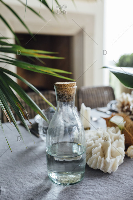 Glass water carafe on tropical table