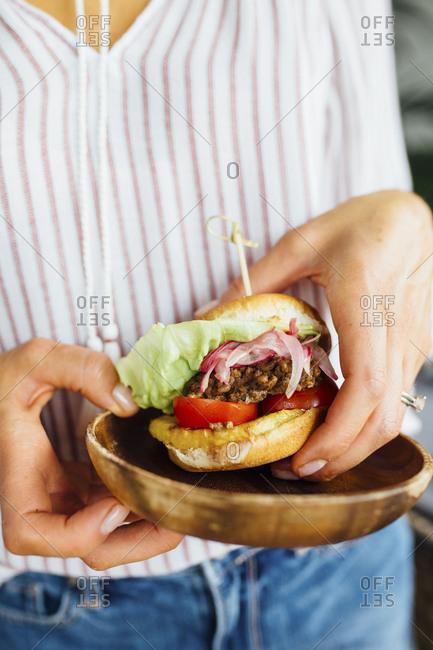 Woman holding slider burgers