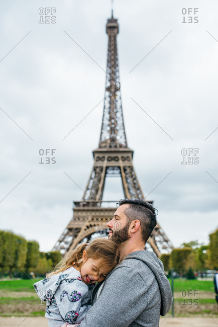 Father embraces his laughing daughter at the Eiffel tower, Paris