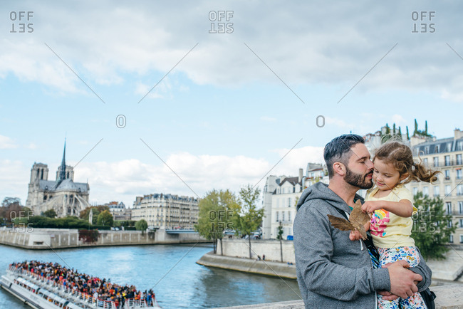 Father holds daughter along the banks of the Seine, Paris