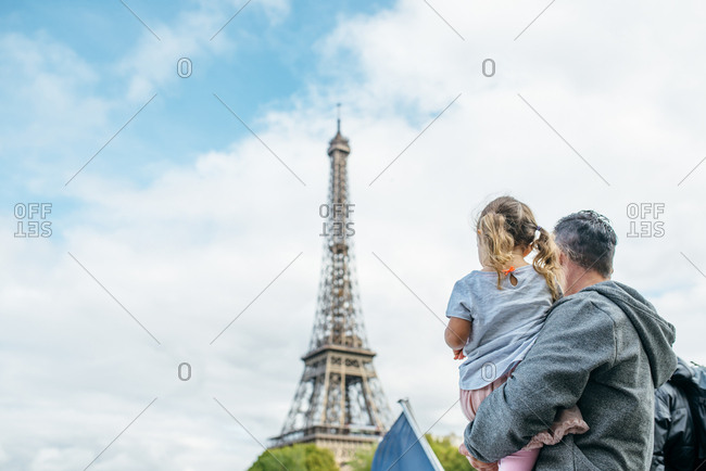 Father and his daughter looking at the Eiffel tower, Paris