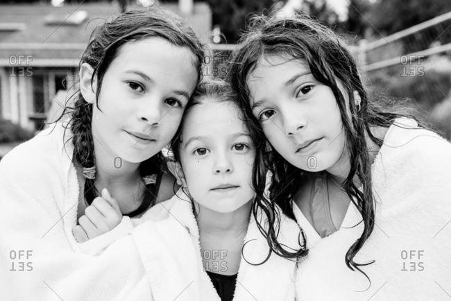Three girls share a towel after a swim